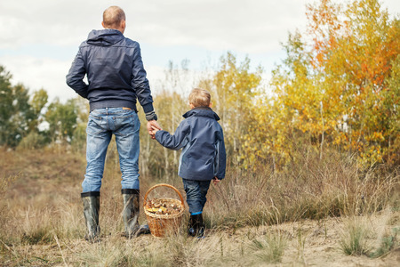 Son and father with full basket of mushrooms on the forest glade
