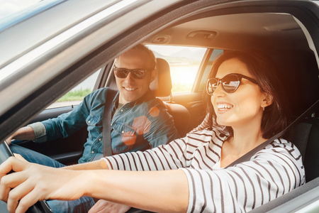 행복한 커플이 차를 타고 간다.
