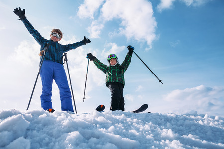 Two happy skiers stay together on the top of snow hill