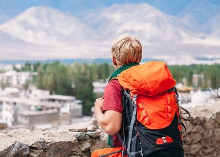 Backpacker tourist looks on blue mountain Stock Photo
