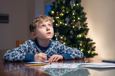 ded moroz: Little boy write Christmas wishes to Santa Stock Photo