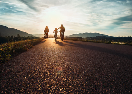 Ð¡yclists family traveling on the road at sunset Foto de archivo