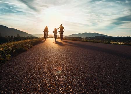 niños en bicicleta: ?yclists familia que viaja en el camino al atardecer Foto de archivo