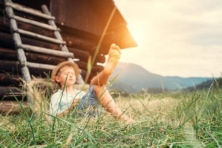 shoeless: Boy sleeps in grass under hayloft in summer afternoon