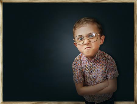 the pupil: Emotional pupil boy near chalkboard Stock Photo
