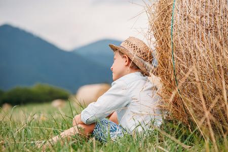 hayroll: Boy sits near big hayroll on the field