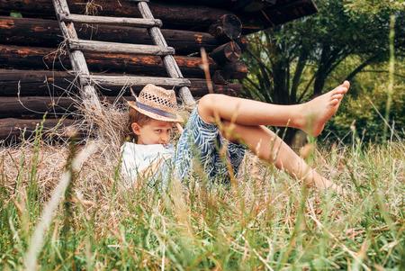 shoeless: Summer in the countryside - little boy lies near the hayloft