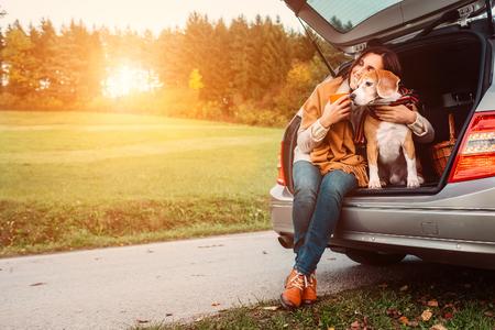 여자와 강아지 가을 도로에서 자동차 트렁크 앉는다. 스톡 콘텐츠