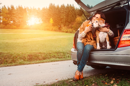 Woman with dog sits in car trunk on autumn road 版權商用圖片 - 65053813