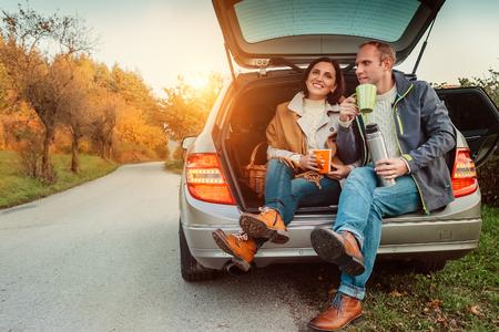 부부는 자동차 여행 중에 차 휴식을 취합니다.