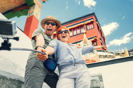 Happy tourist couple take a selfie photo on asian sight background