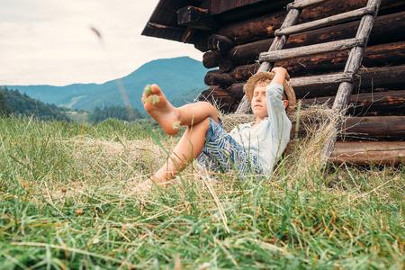 boy kid: Boy sleeps in hay under the old barn