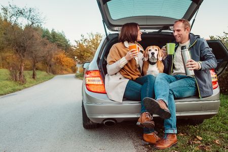Tea party in car trunk - loving couple with dog sits in car trunk