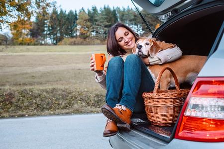彼女の犬と女性の秋の自動車旅行の間にお茶の時間があります。