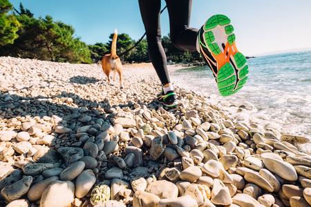 Close-up beeld canicrosser benen weared lopen schoenen op de zee Stockfoto