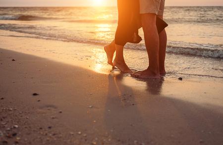 honey moon: Close up image in love couple legs on sun rise sea side Stock Photo
