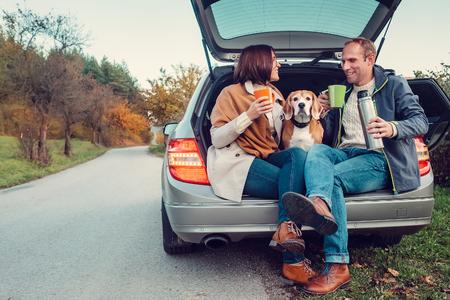 Tea party dans un coffre de voiture - couple aimant avec un chien se trouve dans un coffre de voiture