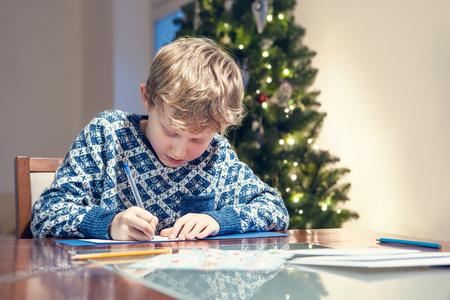 ded moroz: Little boy write a congratulations christmas card Stock Photo