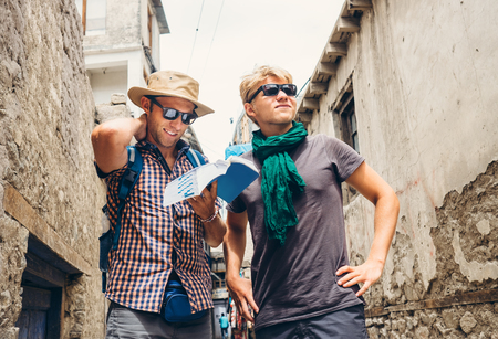 guidebook: Two tourists try to navigate with guidebook on unknown asian street Stock Photo
