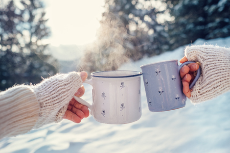 drink coffee: Man and woman hands in knitting mittens with cups of hot tea on winter forest glade Stock Photo