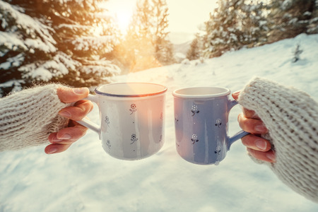 Couple hands in mittens take a mugs with hot tea in winter forest
