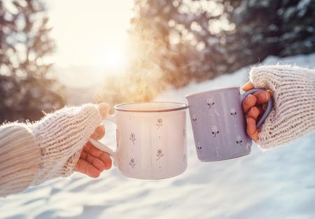 tomando café: El hombre y la mujer de las manos en guantes de tejer con las tazas de té caliente en el claro del bosque del invierno