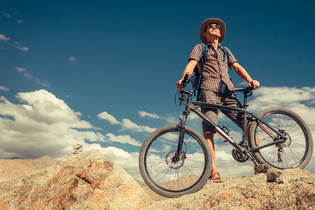 Bikeer traveler with bicycle portrait in Himalayas mountain