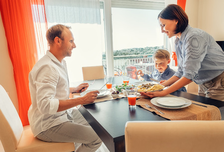 dinner food: Mother brings a dish of meal at table to her hungry family