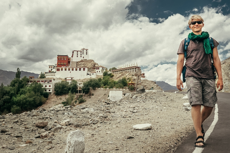 Young tourist man walks on road near Thiksey Monastery in India, Ladakh Stock Photo