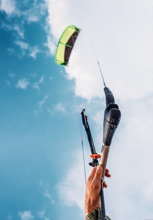 kite surfing: Close up image kitesurfers hand with kite in blue sky