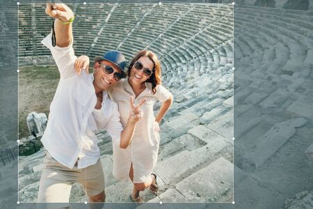 social history: Funny couple take a selfie photo in antique amphitheatre in Side, Turkey