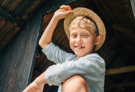 ranch house: Carefree boy in straw hat