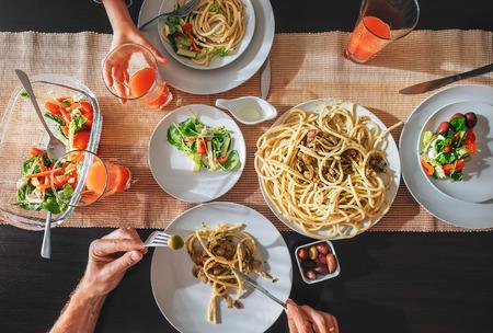 Gezin verse diner met grapefruitsap, pasta en salade