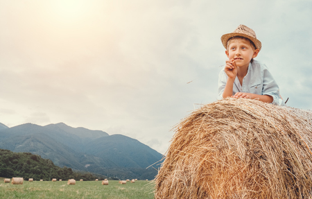 Boy in sraw hat lying on hay roll