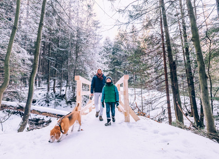 Father and son walk with dog in snow forest