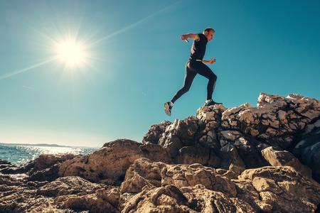남자는 바위 같은 바다 쪽에서 달린다. 스톡 콘텐츠