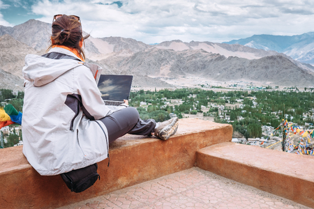 learning online: Traveler with laptop sits on top view point on the mountain valley