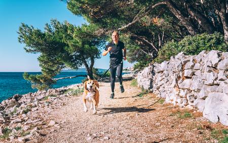 남자는 개가 바다 근처에서 뛰다. 스톡 콘텐츠