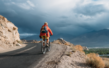 Bike tourist rides on Himalaya mountain road on way to buddist monastery Stock Photo