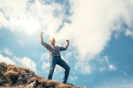 masters of rock: Triumphed man on the top of mountain peak Stock Photo