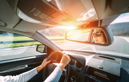 Vrouw besturen van een auto weerspiegelt in de rug view mirror