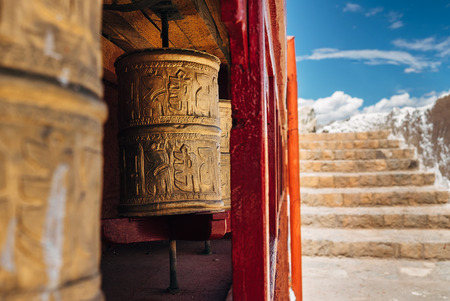 Tibetan prayer wheels with a stairs background