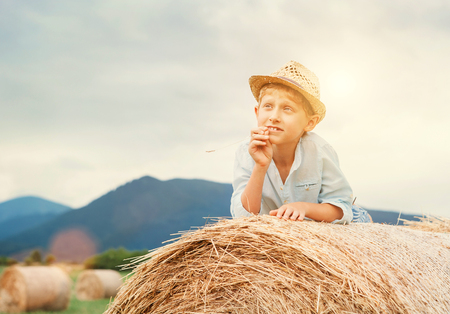 Dreaming boy lying on the rolling haystack Stock Photo