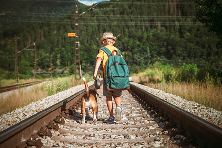 emty: Little boy with backpack walks with beagle dog on the emty railway in forest