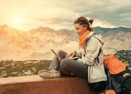 Backpacker met laptop zit op het bovenaanzicht punt onder de bergen AFWIKKELING