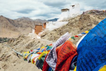 Tibetan prayer flags with Tsemo Monastery in Leh on background