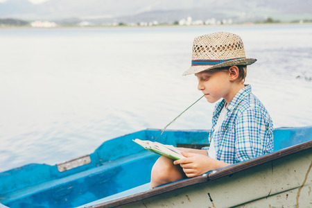 educating: Boy reads a book in old boat on the lake bank