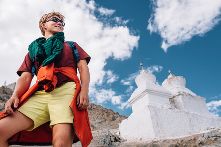 Young man tourist portrait with buddhist holy stupas on background