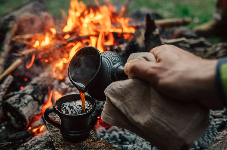 Making coffee process on the campfire. Man pour coffe in clay cup
