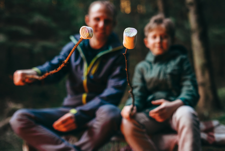 Father and son prepare to bake marshmallow candies on campfire